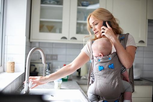 Woman holding baby while on her cell phone