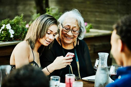 Grandchild with grandmother looking at cell phone